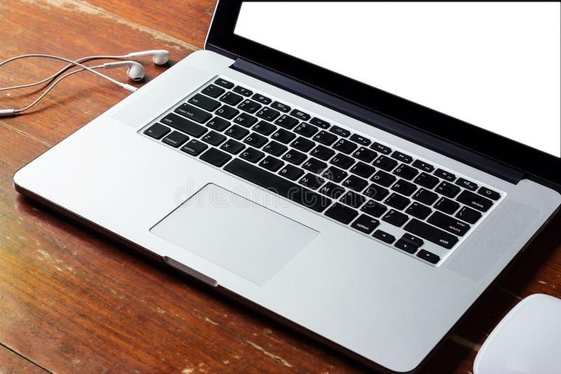 Pantalla blanca en blanco del ordenador portátil y auricular blanco en la tabla de madera de madera foto de archivo