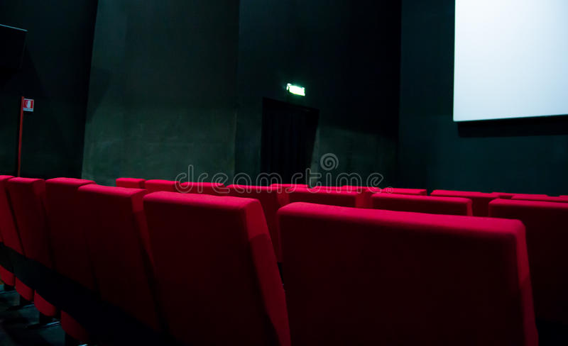 Pantalla de cine y sillas rojas dentro de un cine fotografía de archivo
