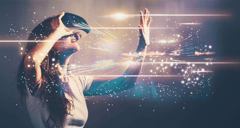 Pantalla de Digitaces con la mujer joven con VR foto de archivo