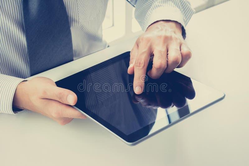Pantalla de la PC de la tableta conmovedora de la mano del hombre de negocios en la tabla fotos de archivo