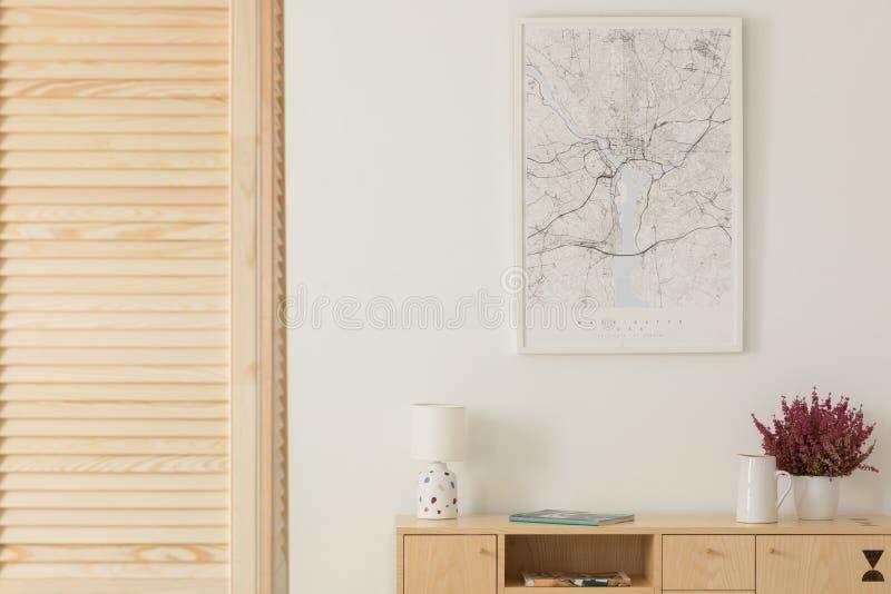 Pantalla de madera al lado del gabinete de madera con la lámpara, el florero y el brezo en el pote blanco, mapa en el marco blanc imagenes de archivo