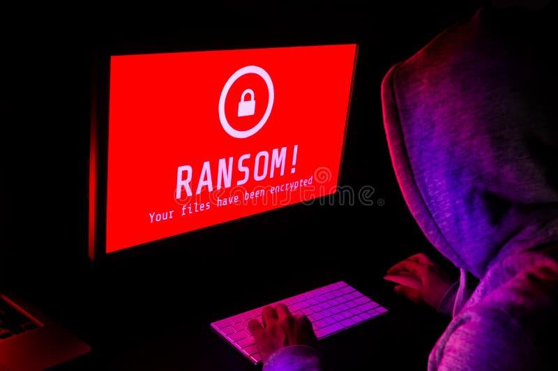 Pantalla de ordenador con alarmas del ataque del ransomware en rojo y un hacke