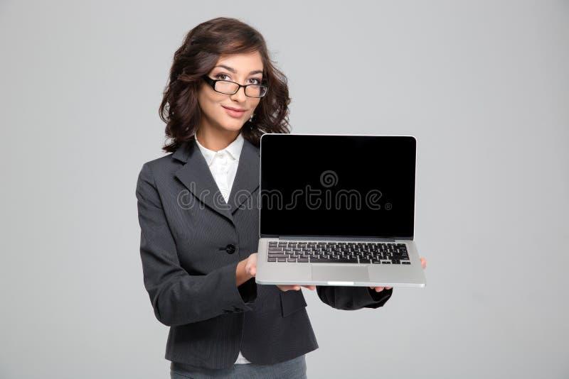 Pantalla de ordenador portátil bastante femenina confiada del espacio en blanco de la demostración fotografía de archivo libre de regalías