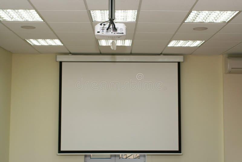 Pantalla de proyección en la sala de reunión con el retroproyector fotografía de archivo libre de regalías