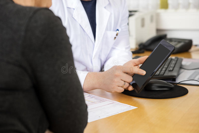 Pantalla del doctor Touching Digital Tablet mientras que paciente que asiste foto de archivo