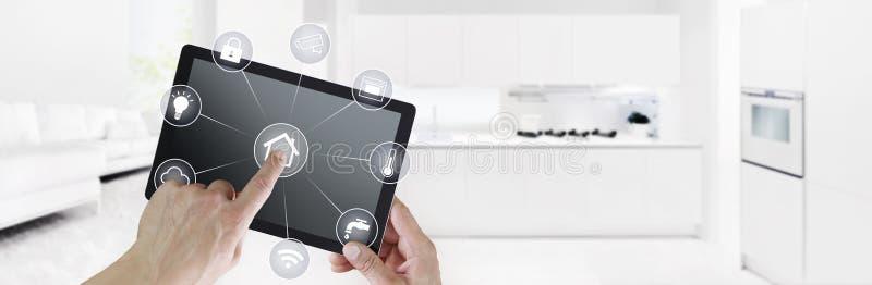 Pantalla digital de la tableta de la automatización casera del control del tacto elegante de la mano con los símbolos blancos en  imagen de archivo