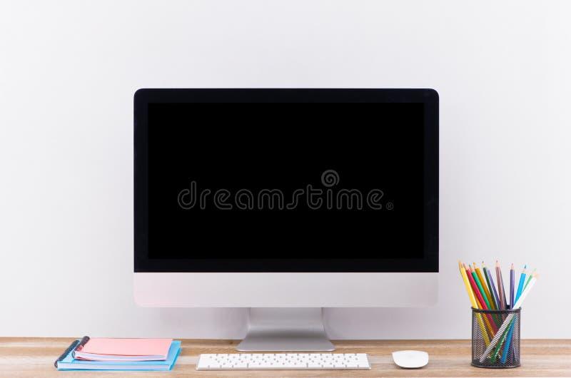 Pantalla en blanco blanca del ordenador portátil en vista delantera de la tabla de trabajo foto de archivo libre de regalías