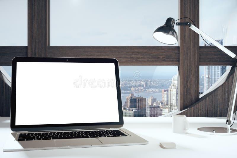 Pantalla en blanco del ordenador portátil en sitio moderno con la ventana, la lámpara y c redondas imagen de archivo