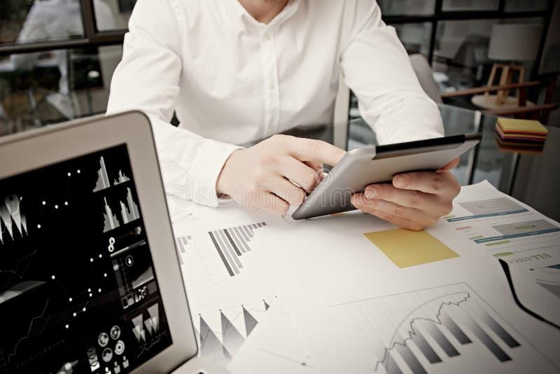 Pantalla moderna conmovedora de la tableta del hombre de negocios de la foto Encargado del comerciante que trabaja la nueva ofici fotografía de archivo