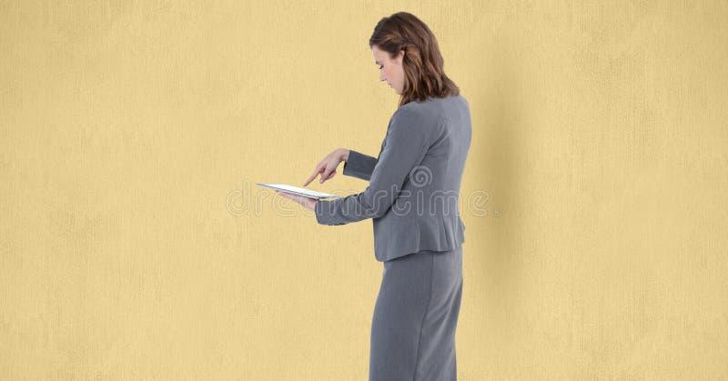 Pantalla táctil de la empresaria de la tableta sobre fondo beige imagenes de archivo