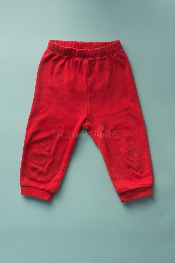 Pantalon rouge de sports de bébé sur le fond bleu photo libre de droits