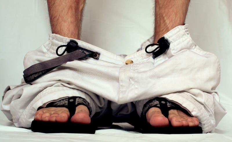 Pantalon vers le bas sur des santals photos stock