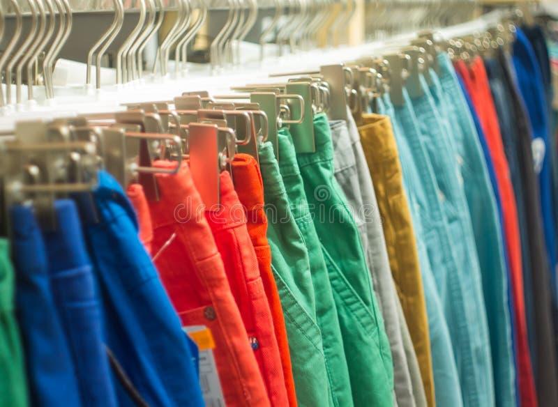 Pantalones coloridos que cuelgan en venta en tienda fotografía de archivo libre de regalías