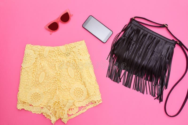 Pantalones cortos amarillos del cordón, bolso negro con la franja, smartphone y vidrios rosas Fondo rosado brillante fotos de archivo