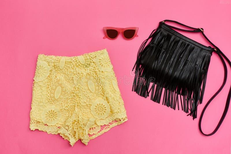 Pantalones cortos amarillos del cordón, bolso negro con la franja y vidrios rosas Fondo rosado brillante foto de archivo libre de regalías