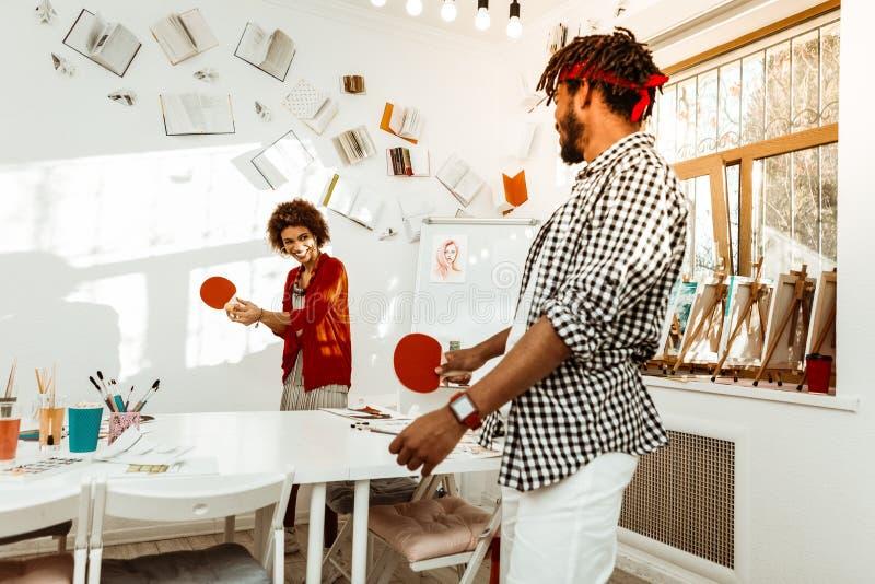 Pantalones cortos blancos que llevan del novio barbudo que juegan a tenis con la novia imagen de archivo libre de regalías