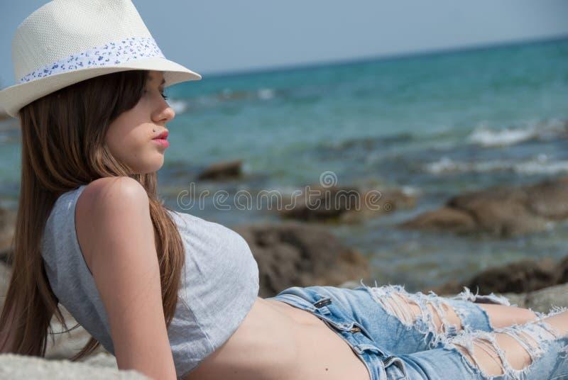 Pantalones cortos de la chica joven y top y sombrero de la cosecha que llevan que presentan afuera fotos de archivo