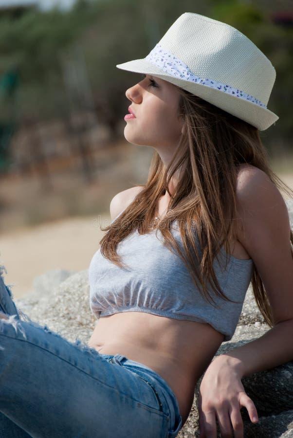 Pantalones cortos de la chica joven y top y sombrero de la cosecha que llevan que presentan afuera fotografía de archivo