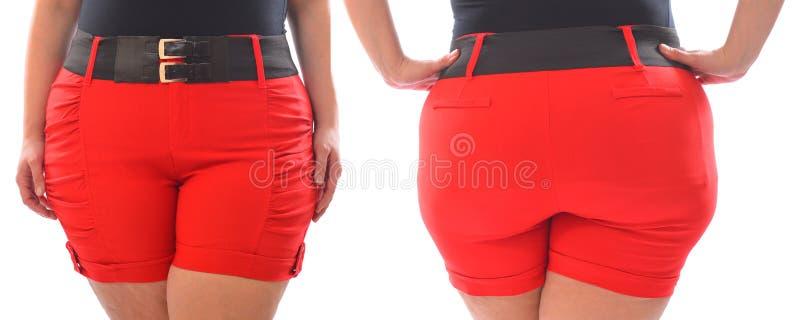 Pantalones cortos rojos de la mujer de XXL con la correa negra en el modelo del tamaño extra grande aislado en blanco foto de archivo libre de regalías
