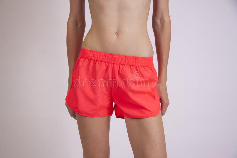 Pantalones cortos rojos de la ropa de playa en mujer imagenes de archivo