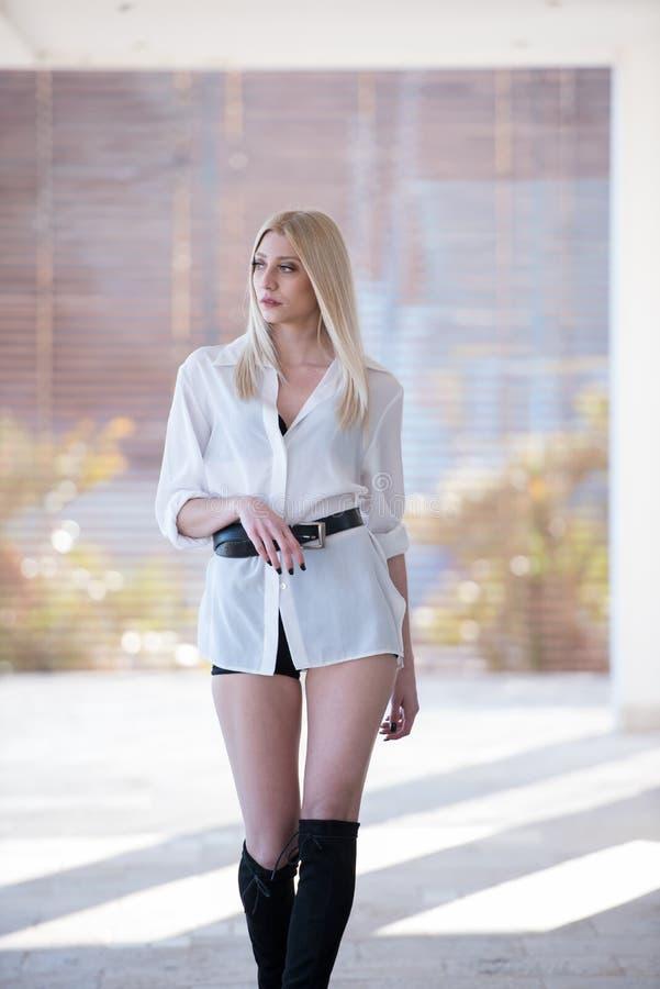 Pantalones cortos rubios atractivos del negro del desgaste de mujer y camisa blanca larga foto de archivo libre de regalías