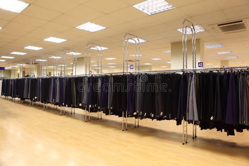 Pantalones de los hombres de la fila en perchas en departamento imagen de archivo