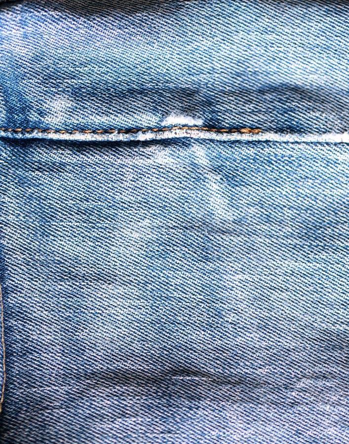 Pantalones vaqueros viejos Puntadas desgastadas del dril de algodón Material lamentable fotografía de archivo
