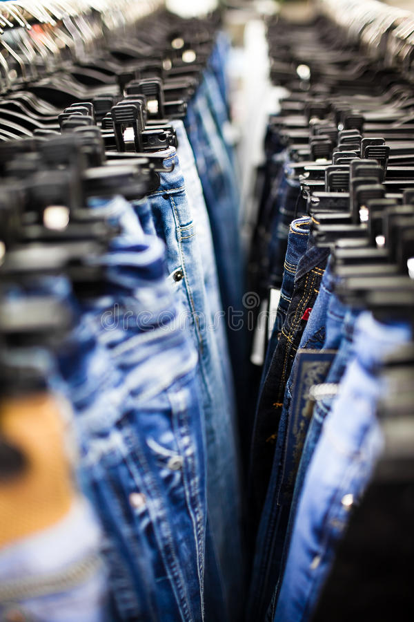 Pantalones vaqueros y pantalones en perchas imágenes de archivo libres de regalías