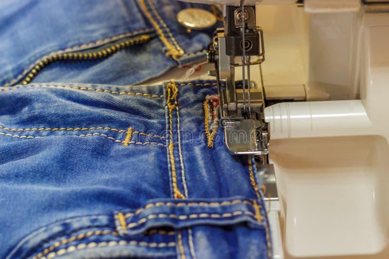 Pantaloni dei jeans di riparazione della macchina per cucire, primo piano fotografia stock libera da diritti