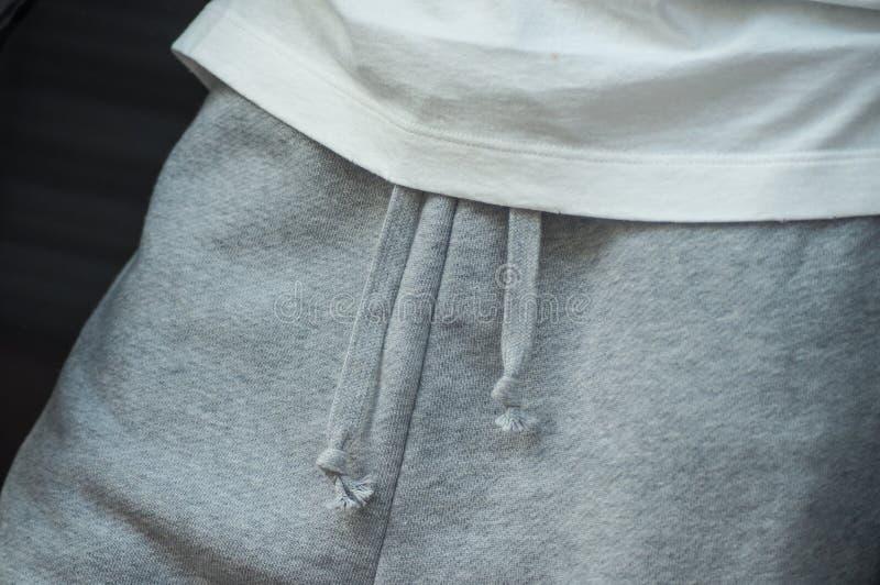 pantaloni grigi e maglietta bianca nel deposito di usura di sport immagini stock libere da diritti
