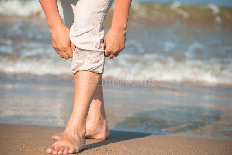 Pantaloni maschii scalzi di pieghettatura fotografia stock libera da diritti
