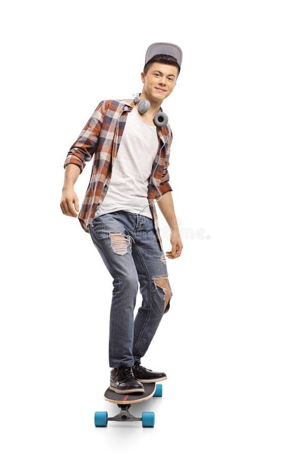 Pantaloni a vita bassa adolescenti che guidano un longboard fotografia stock libera da diritti