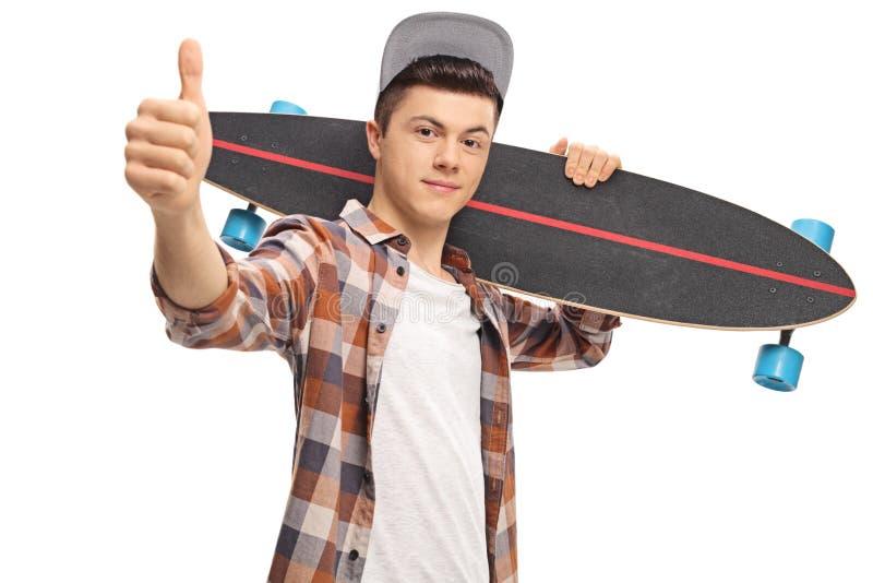 Pantaloni a vita bassa adolescenti con un longboard che fa un pollice sul segno fotografia stock