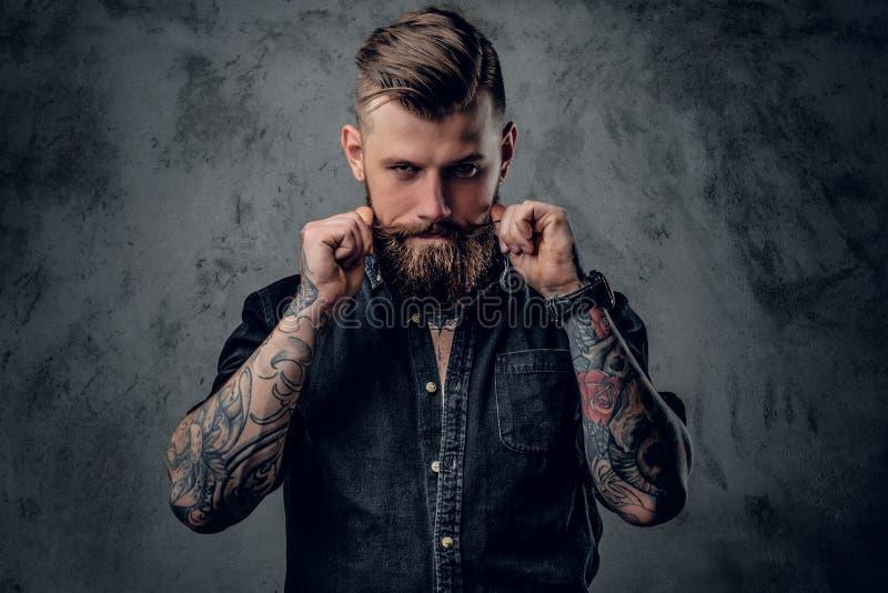Pantaloni a vita bassa barbuti con tattooe sul suo armi immagini stock