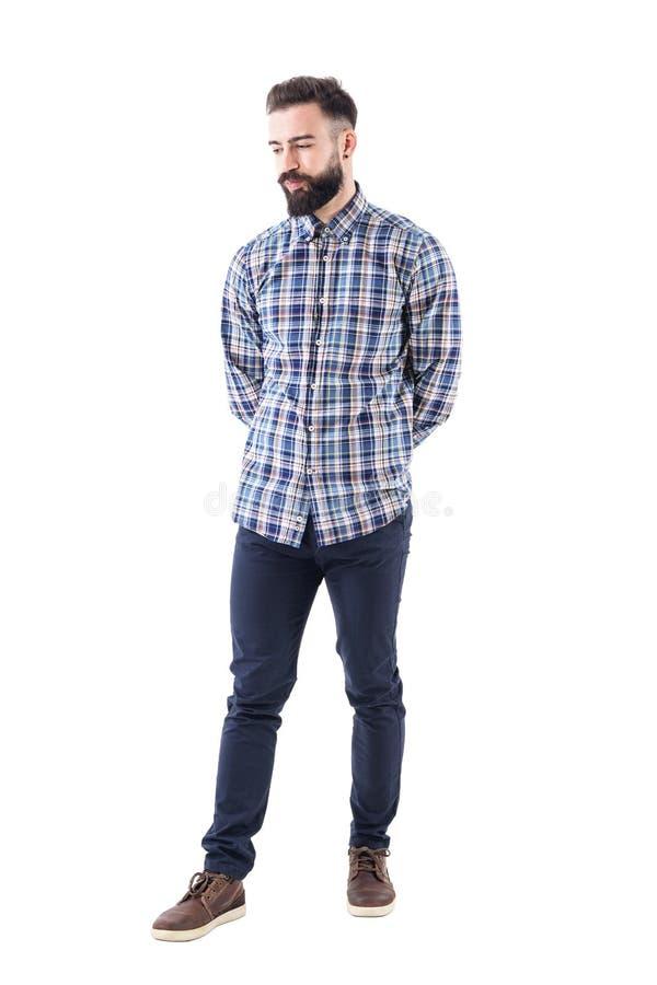 Pantaloni a vita bassa barbuti scettici deludenti con le mani sulla parte posteriore che guarda giù fotografia stock libera da diritti