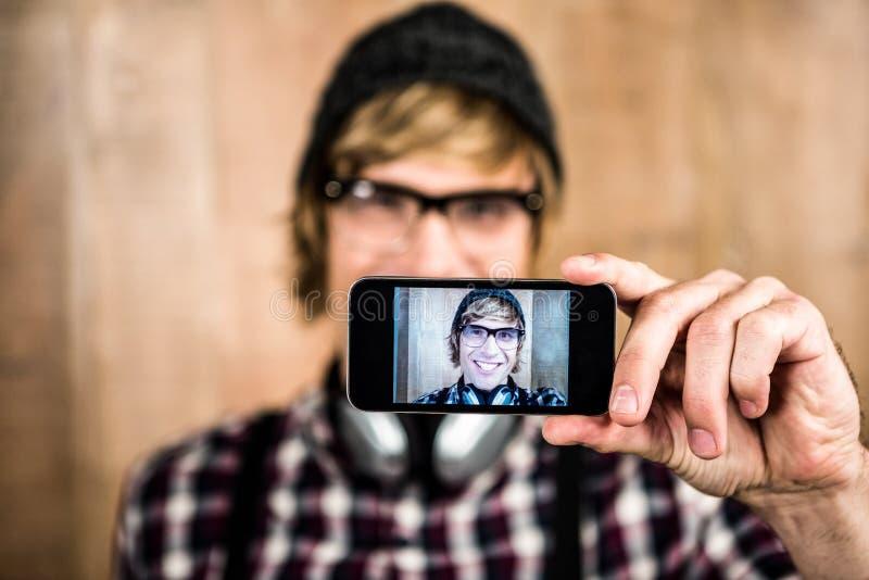 Pantaloni a vita bassa biondi sorridenti che prendono selfie fotografia stock