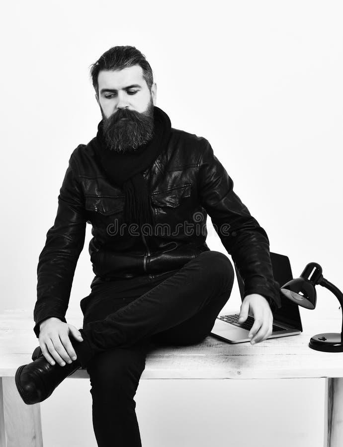 Pantaloni a vita bassa caucasici brutali barbuti che si siedono sulla tavola con il computer portatile sopra immagini stock libere da diritti