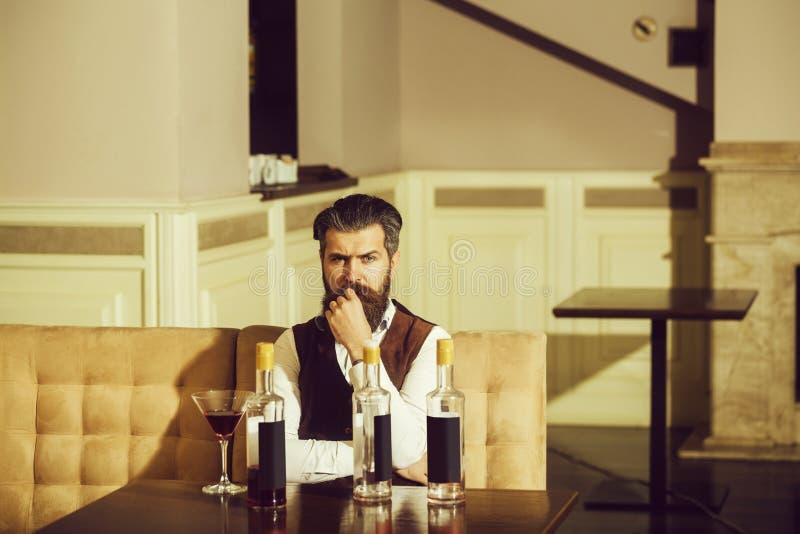 Pantaloni a vita bassa che si siedono sul sofà con il vetro di martini e tre bottiglie fotografia stock libera da diritti