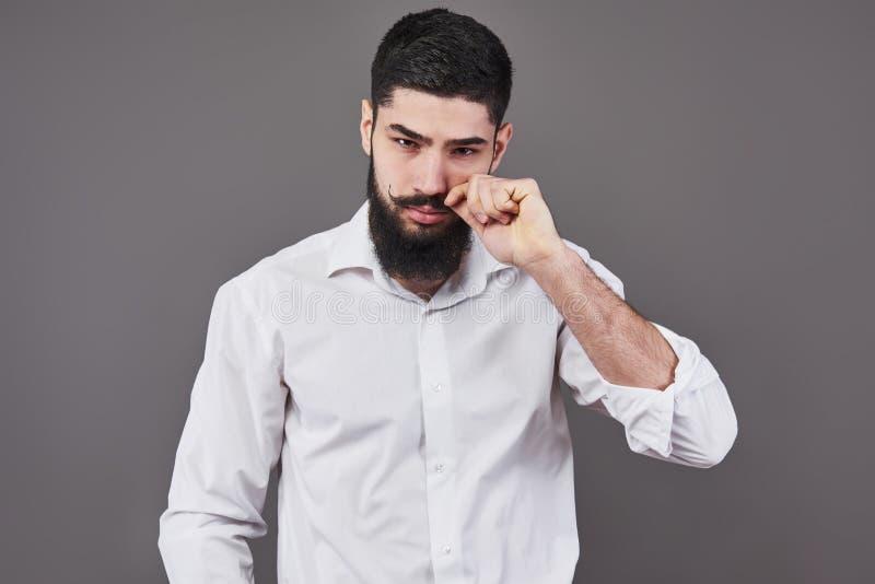 Pantaloni a vita bassa con il fronte serio sensibilità ed emozioni Tipo o uomo barbuto su fondo grigio Modo e bellezza del barbie immagini stock