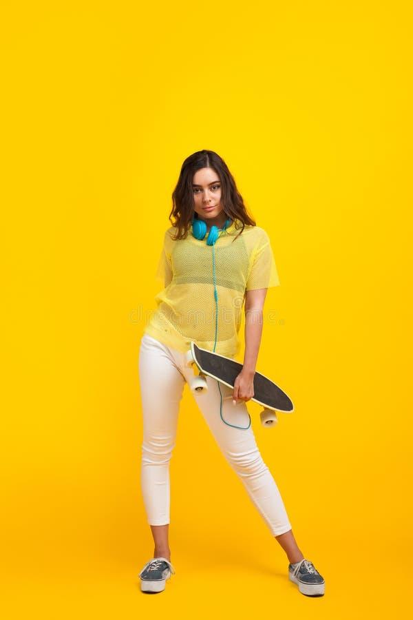 Pantaloni a vita bassa d'avanguardia che posano con il longboard fotografia stock libera da diritti