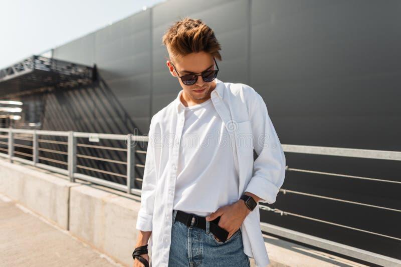 Pantaloni a vita bassa d'avanguardia del giovane in vestiti alla moda in occhiali da sole neri con un resto dell'acconciatura sul fotografia stock