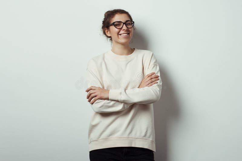 Pantaloni a vita bassa sorridenti bei della donna che indossano i vetri in bianco dell'occhio e del maglione Fondo vuoto della pa immagini stock