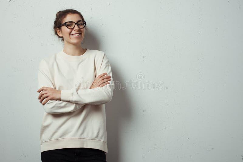 Pantaloni a vita bassa sorridenti bei della donna che indossano i vetri in bianco dell'occhio e del maglione Parete di lerciume c fotografia stock libera da diritti