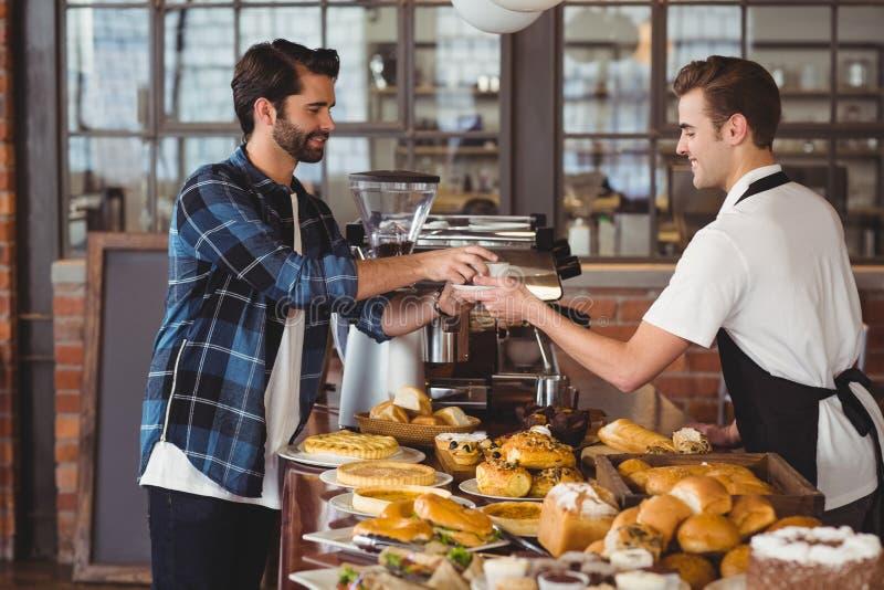 Pantaloni a vita bassa sorridenti che ottengono tazza di caffè dal barista immagine stock