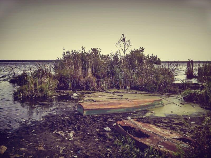 Pantano deshabitado terrible con los barcos abandonados viejos Fondo natural para las ideas místicas del diseño asustadizo foto de archivo