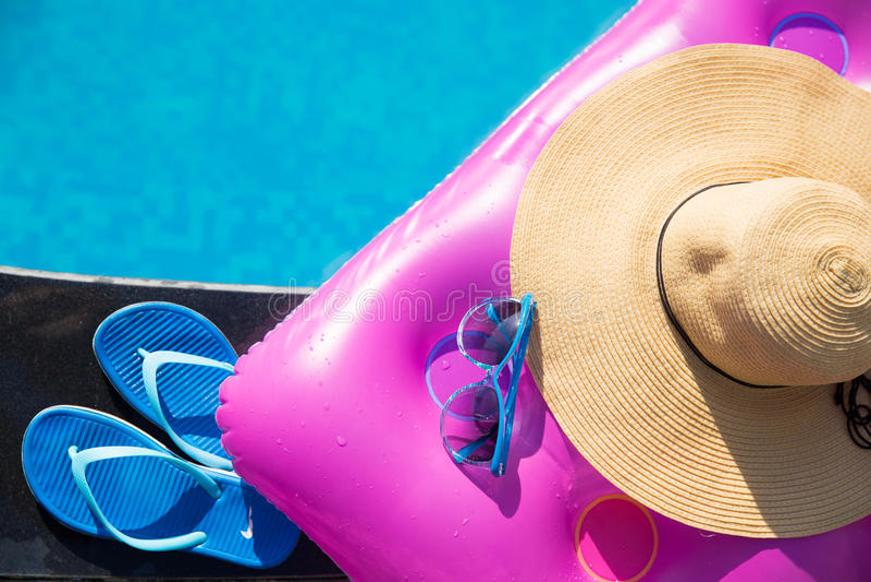 Pantoffels, zonnebril, strohoed en luchtmatras stock afbeelding