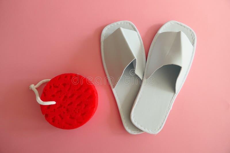 Pantofole bianche della stazione termale con la nuova spugna rossa su fondo rosa fotografie stock