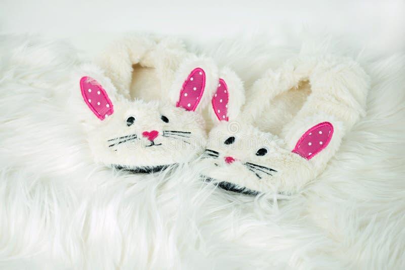 Pantofole del coniglietto su pelliccia bianca fotografia stock