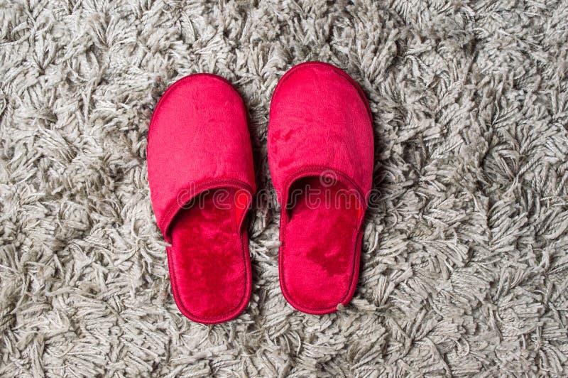 Pantofole di casa rosse su tappeto grigio immagini stock libere da diritti