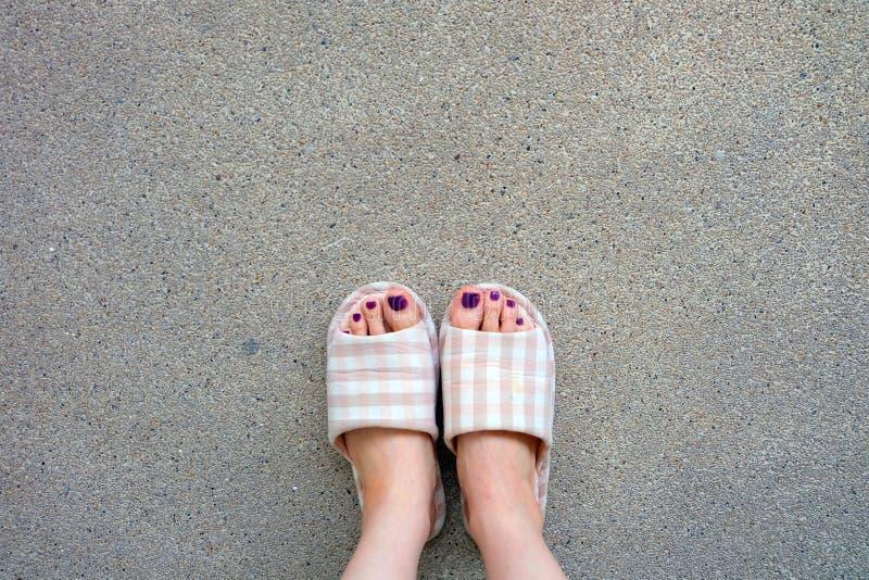 Pantofole a quadretti, smalto dei piedi delle pantofole della casa di rosa di Selfie Woman's su fondo concreto fotografia stock libera da diritti